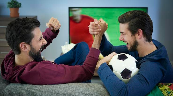 Two friends watching football