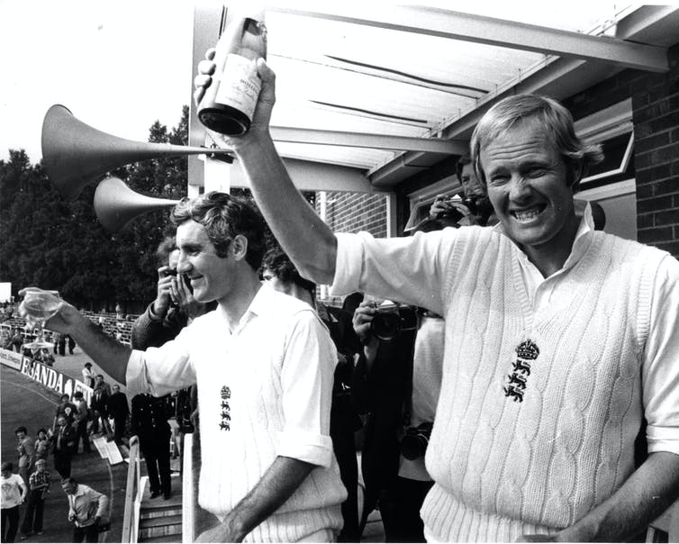 Black and White picture of two men in cricket gear with a trophy.