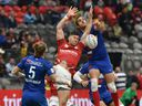Canada (red) and France battle for the ball during the HSBC World Rugby Sevens Series at B.C. Place stadium in Vancouver on March 7, 2020.