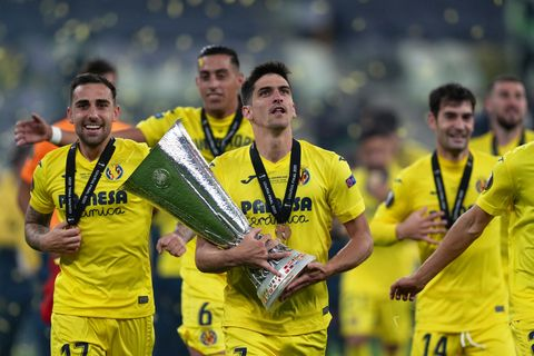 villareal's gerard moreno cradles the uefa europa league trophy as he walks with his teammates