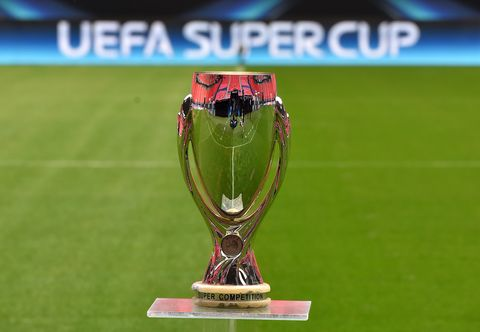 the uefa super cup trophy on a plinth positioned on an empty football pitch, the stand opposite is reflected in the cup, which has the words 'super competition' written on its base